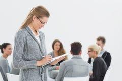 治疗师与小组疗法的文字笔记在会议上 免版税图库摄影
