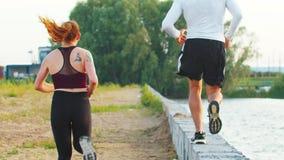 沿一个具体壁架的嬉戏夫妇奔跑沿往绿色森林的堤防 股票视频