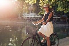 沿一个池塘的有吸引力的少妇骑马自行车在城市公园 免版税库存图片
