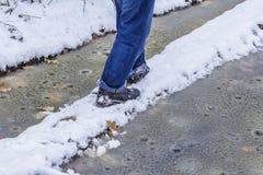 沿一个狭窄的道路危险冬天供以人员走在下雨天 库存图片