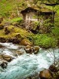 沿一条山小河的腐朽的谷仓在意大利阿尔卑斯 库存照片