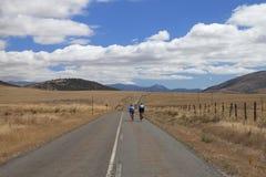 沿一条离开的路的骑自行车者 免版税库存图片