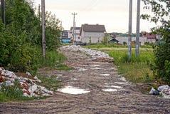 沿一棵农村路、草和树的垃圾在私有房子前面 免版税库存图片