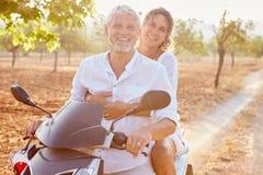 沿乡下公路的成熟夫妇骑马小型摩托车 图库摄影