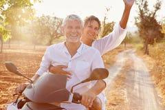 沿乡下公路的成熟夫妇骑马小型摩托车 库存照片