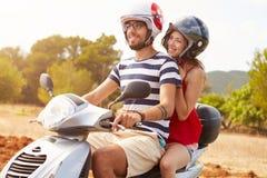 沿乡下公路的年轻夫妇骑马小型摩托车 免版税库存照片