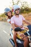 沿乡下公路的年轻夫妇骑马小型摩托车 库存照片
