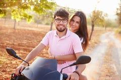 沿乡下公路的年轻夫妇骑马小型摩托车 库存图片