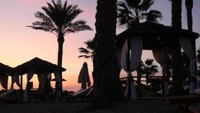 沿休息室区域的好的家庭步行与棕榈树和帐篷的塞浦路斯海滩的在美好的日落 股票录像