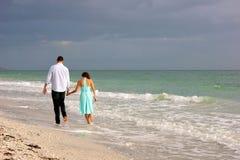 沿作为海滩bonita夫妇日落走的年轻人 免版税库存照片