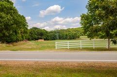 沿农场马路的篱芭在乡下 免版税库存图片