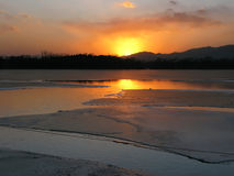 沿冰冷的河的日落 免版税库存照片