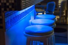 沿在蓝色光照亮的酒吧的空的凳子 免版税库存照片