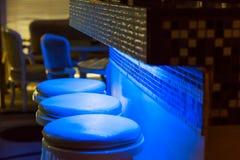 沿在蓝色光照亮的酒吧的空的高凳 免版税库存照片