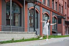 沿城市窗口的年轻孕妇走的跳舞 免版税库存图片