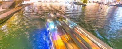 沿塞纳河的快行渡轮在巴黎在晚上- Fra 免版税库存图片