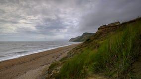 沿多西特海岸的看法从在Eype附近的海滩在与使海光滑和弄脏蕨的长的曝光的一个大风天, 库存图片