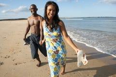 沿夫妇浪漫海岸线走的年轻人 免版税库存图片