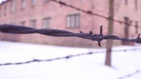 沿奥斯威辛比克瑙集中和灭绝阵营老生锈的铁丝网篱芭走 的砖营房 影视素材