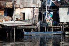 沿家菲律宾河简陋小木屋蹲着的人 免版税库存图片