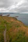 沿小山的道路在威克洛爱尔兰北部港口防堤墙壁和灯塔上 免版税库存图片
