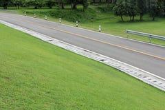 沿山坡绿草的乡下公路 免版税库存图片