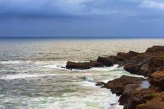 沿岩石沿海岸的风暴使变暗的天空 库存图片