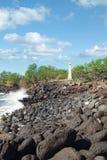 沿岩石火山的岸的小灯塔 免版税库存图片
