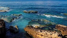 沿岸航行与岩石在海,明白蓝色和绿宝石色的水 库存照片