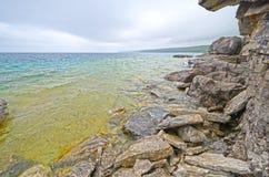 沿峭壁的色的水 免版税库存图片