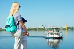 沿散步的母亲和儿子步行和看看漂浮在河的船 免版税库存照片