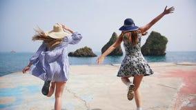 沿散步跑的两年轻女人直接地到水的海在好日子 股票视频