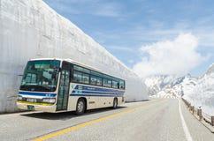 沿日本阿尔卑斯雪墙壁的游览车移动在馆山kurobe高山路线 免版税库存图片
