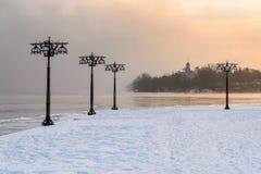 沿有薄雾的河的斯诺伊堤防有在有雾的日出的灯笼的-冬天风景 我 图库摄影
