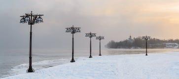 沿有薄雾的河的斯诺伊堤防有在有雾的日出的灯笼的-冬天风景 库存照片