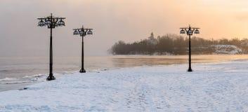 沿有薄雾的河的斯诺伊堤防有在有雾的日出的灯笼的-冬天风景 II 库存图片