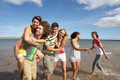 沿朋友组海岸线走的年轻人 免版税库存图片