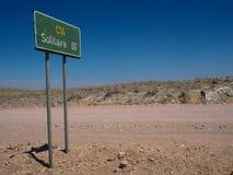 沿未铺砌的土路C14的绿色定向路标杆向在岩石沙漠风景中的单粒宝石与蓝天 免版税库存照片
