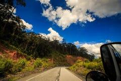 沿树木繁茂的小山的柏油路在公共汽车窗口蓝天外面 库存图片