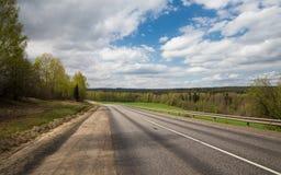 沿森林的一条离开的乡下公路在与云彩的蓝天下 免版税库存照片