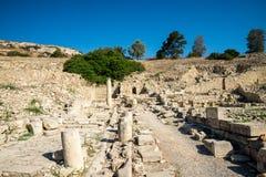 沿残破的专栏的一条漫长的路对一个被成拱形的门在末端在Amathus,塞浦路斯 免版税图库摄影