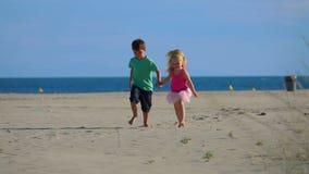 沿沙子的小男孩和女孩奔跑从海 影视素材