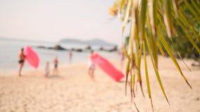 沿沙滩的年轻朋友奔跑与在热带海岛上的可膨胀的空气沙发吊床 4K 普吉岛泰国 股票录像