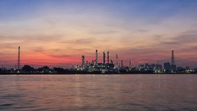 沿河的炼油厂日出的 免版税库存图片