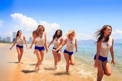沿浅水区和微笑的啦啦队员奔跑 免版税库存图片
