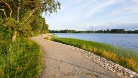 沿海一个湖的一条平安的小径在日落期间在与美好的绿色植被的夏天 图库摄影