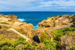 沿海岩石形成了砂岩美丽如画的曲拱  澳大利亚的大洋路  免版税库存照片