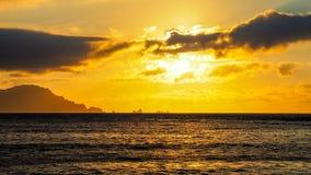 沿海日落,在云彩之间 免版税库存图片