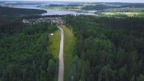 沿海森林镇顶视图  夹子 农村路在导致海滨城镇的森林里 住在接近自然的镇  股票录像