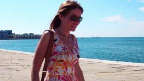沿海滨人行道的年轻女人佩带的太阳镜步行 影视素材